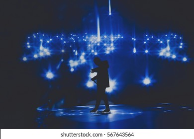 Rap & trap & hip hop star / singer perform on stage of nightclub in front of bright screen with stars. Music hall performing arts event. Dark background, smoke, concert  spotlights