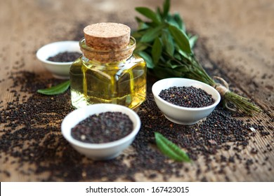 rape oil in a vessel with seeds on a wooden background