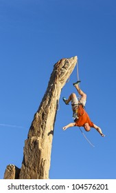 Rapelling climber falling upsidedown from a challenging rock pinnacle.