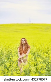 rapeseed field, yellow, red-haired naked girl standing