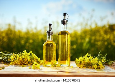 Rapeseed oil bottles (canola) on background rape field