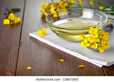 Rapeseed oil and flowers on wood background. Food composition
