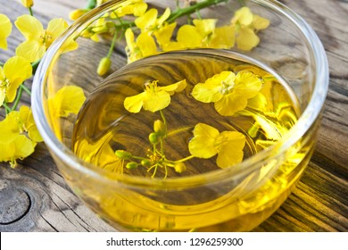 Rapeseed oil and glass bowl with blossoms