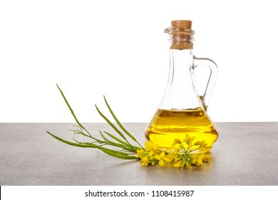 Rapeseed oil in jar with flowers on table.