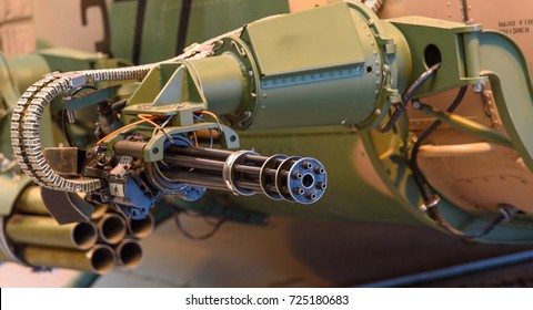 "A rapid fire ""Gatling Gun"" attached to the side of a military helicopter"