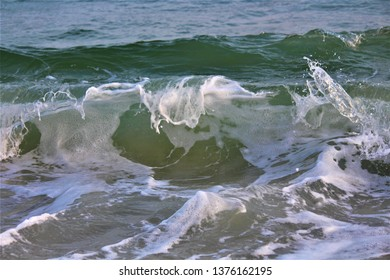 Rapid green waves crash against the shore in Alabama
