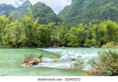 Rapids on the river with waters homeland sloped undulations. People take advantage of hydroelectric water power to provide irrigation water for rice fields