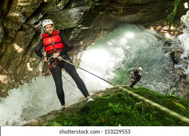Rappel Into A Waterfall Specialized Guid In The Background