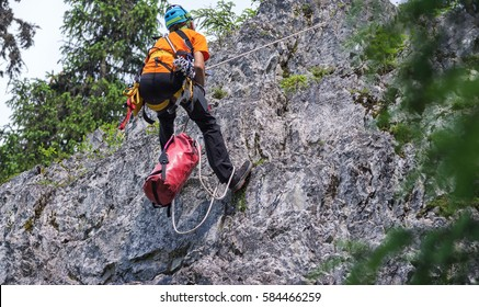 Rappelling a vertical cliff by a climber.