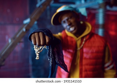 Rapper with gold chain posing in grunge studio