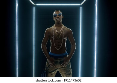 Rapper in gold chains dancing in illuminated cube