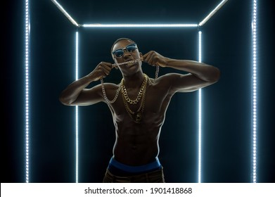 Rapper in gold chains poses in illuminated cube