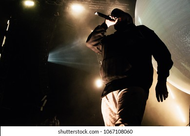 Rapper in hoody with microphone on the stage.
