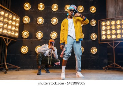 Rappers in caps dance on stage with spotlights