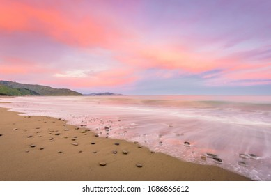 Rarangi Beach, Blenheim, Marlborough, New Zealand: Magical colorful sunset countryside with sandy beach on south island and purple pink cloudy sky and the mountain range of world famous wine region