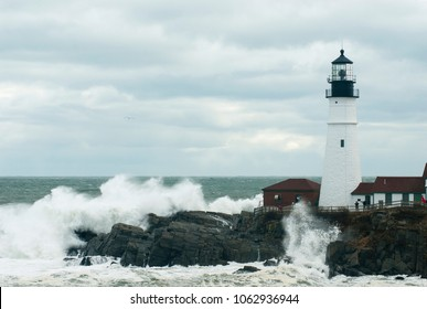 Rare astronomically high tides cause huge waves to break by Portland Head lighthouse in Maine.