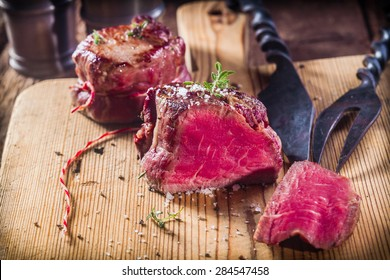 Rare Boar Filets Seasoned with Fresh Herbs on Wooden Cutting Board with Metal Serving Utensils