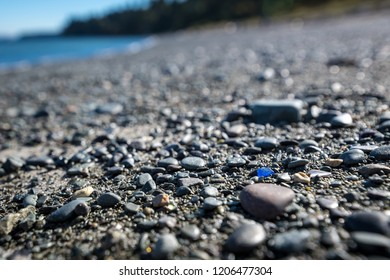 Rare bright blue colored sea glass on the beach amongst pebbles and sand.  Possible concept image for standing out from the crowd and being yourself.
