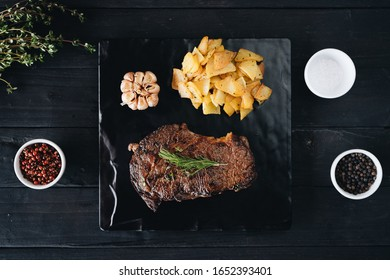 Rare filet mignon beefsteak with roasted potatoes, above view