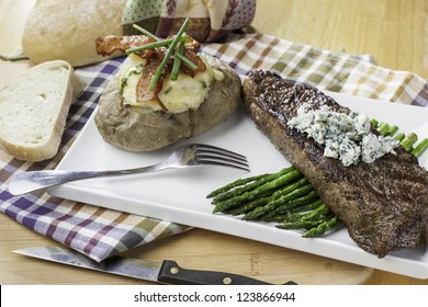 Rare new York strip steak on asparagus topped with bleu cheese with bread and twice baked potato