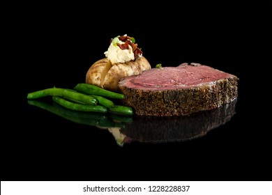 Rare prime rib served with a loaded backed potato and green beans on a black background