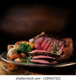 Rare roast beef meal with organic root vegetables and traditional Yorkshire pudding and roast potatoes. Shot against a dark rustic background with generous accommodation for copy space.