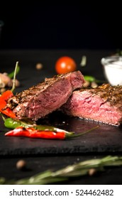 rare steak black rectangular plate pepper on a black wooden background