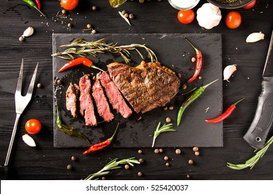 rare steak black square plate spices on a black wooden background top view