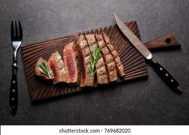Rare steak on cutting board with rosemary and spices. Grilled beef steak top view