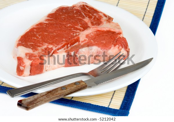 A rare T-bone steak (actually raw) on a plate with silverware, ready for that rare meat lover to eat.