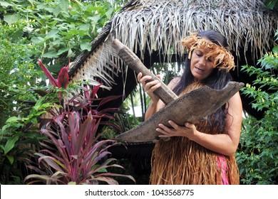 RAROTONGA - JAN 07 2018:Mature Cook Islander woman mashing plants and herbs for herbal medicine in a Maori village in Rarotonga, Cook Islands.