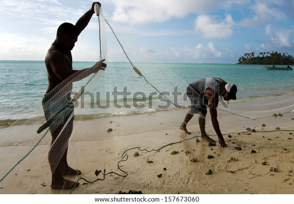 RAROTONGA - SEP 17 2013:Cook Islands fishermen net fishing in Muri lagoon beach.The Cook Islands has rights and responsibilities over 1.8 million square kilometers of ocean.