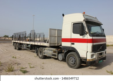 Ras Al Khaimah, United Arab Emirates - August 24, 2019: A flatbed trailer truck designed to carry and transport heavy, huge, wide and bulky cargo or freight, parked on a sandy surface.