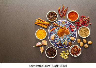Ras el Hanout, exotic luxury spice. Ingredients for preparation oriental spice mix in ceramic bowls. An essential spice for any Moroccan dishes. Stone background copy space top view