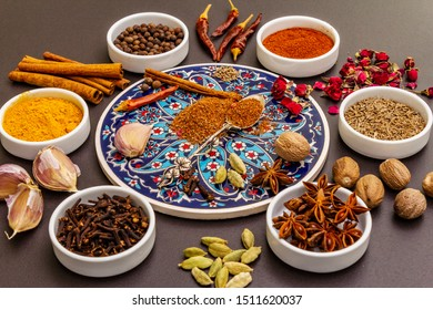 Ras el Hanout, exotic luxury spice. Ingredients for preparation oriental spice mix in ceramic bowls. An essential spice for any Moroccan dishes. Stone background close up