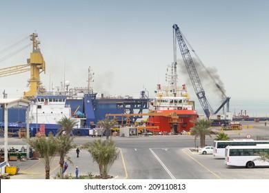 RAS TANURA, SAUDI ARABIA - MAY 13, 2014: Port view with moored ships and workers, Saudi Arabia