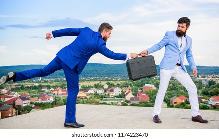 Rascal racketeer extortionist cheating handover. Men suits handover briefcase. Business deal landscape background. Businessman takes away briefcase from business partner. Fraud and extortion concept.