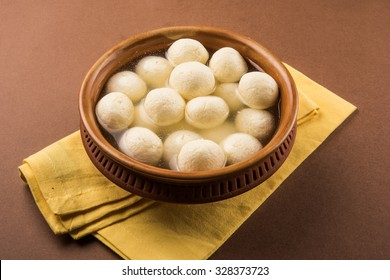 Rasgulla or rosogulla - an Indian sweet made from khoya, soft and spongy, in earthen bowl over yellow napkin and brown background