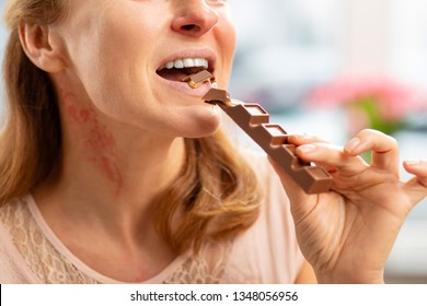Rash and reddening. Blond-haired mature woman with rash and reddening neck eating chocolate bar