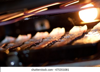 Rashers of streaky bacon being grilled in an oven.