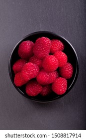Raspberries in a black cup