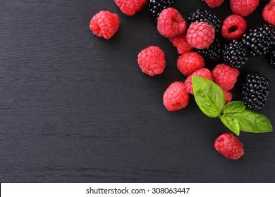 raspberries and blackberries black background