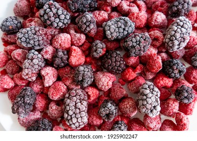 Raspberries and blackberries frozen, berries background. Selective focus
