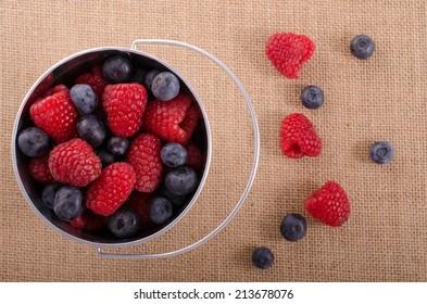 Raspberries and blueberries in  aluminum pale on burlap.