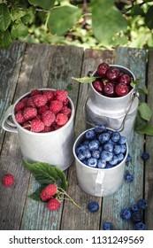 Raspberries, blueberries and cherries in metal mugs on rustic table in garden.