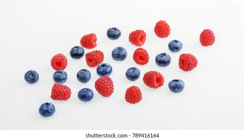 Raspberries and blueberries on white background.  top view