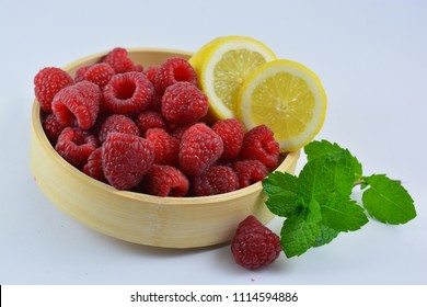 Raspberries in a bowl on a white background