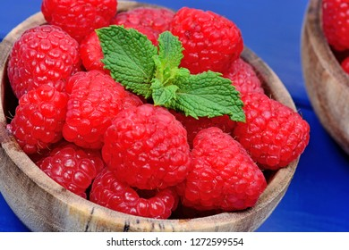 Raspberries in a bowls on blue wood table