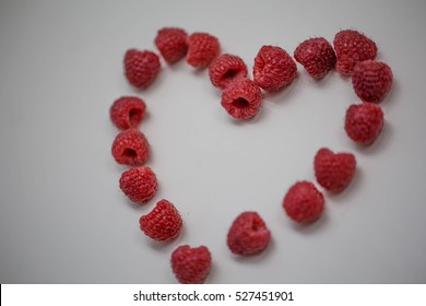 Raspberries in form of Heart on White background