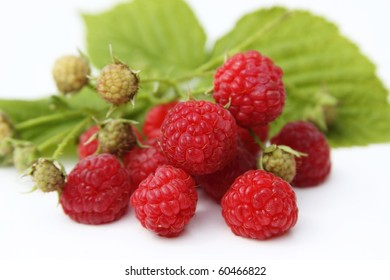Raspberries with leaves isolated on white background